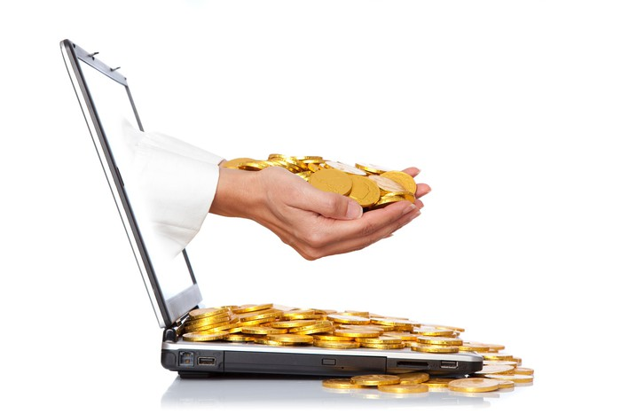 Hands coming out of a laptop holding gold coins.
