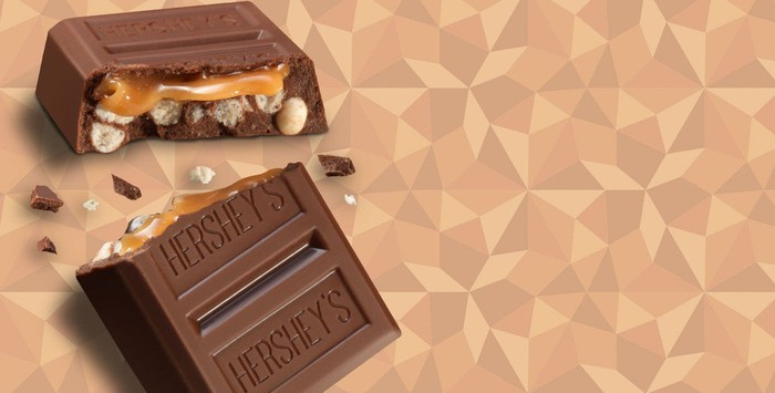 A broken string of three rectangles of Hershey chocolate, revealing caramel and nuts inside.