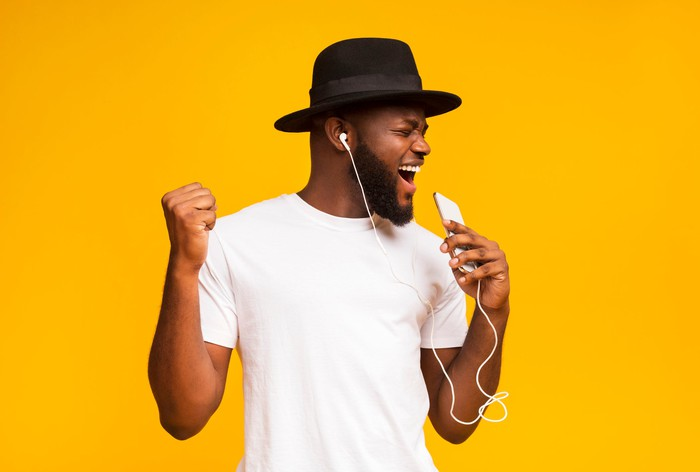 A man listens to music through headphones against an orange background.