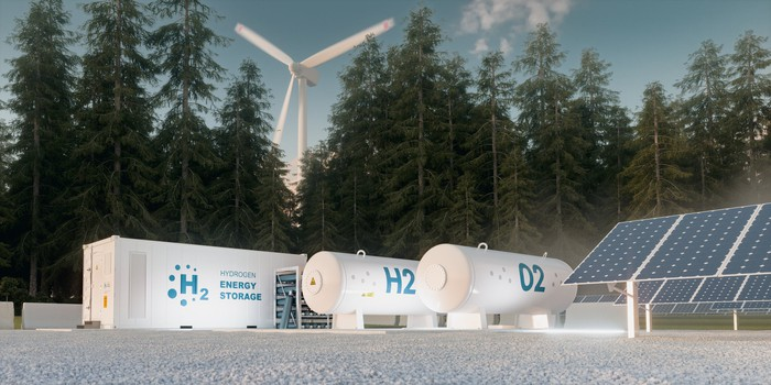 Hydrogen storage tanks near a solar and wind farm with pine trees in the background
