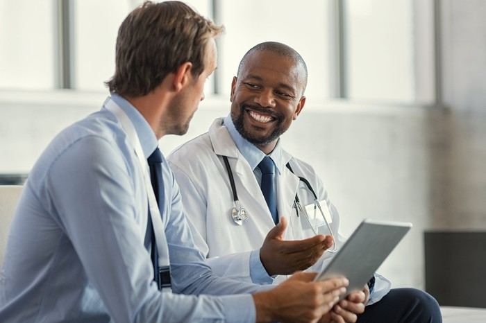 A doctor discussing matters with another person.