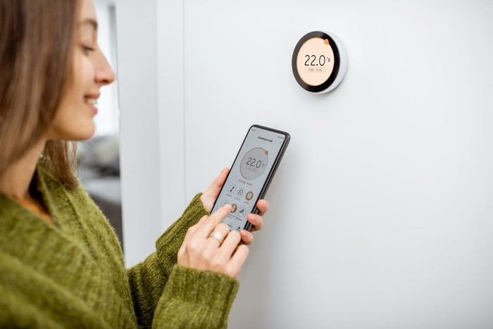 Woman adjusting a thermostat with a smartphone.