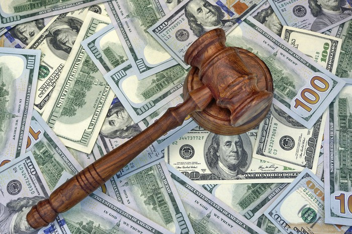 A judge's gavel lying atop a messy pile of one hundred dollar bills.
