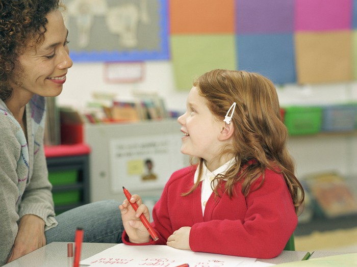 A young student interacting with her teacher.