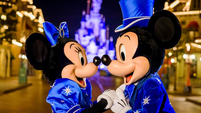 Mickey Mouse and Minnie Mouse nose to nose on Main Street at night.