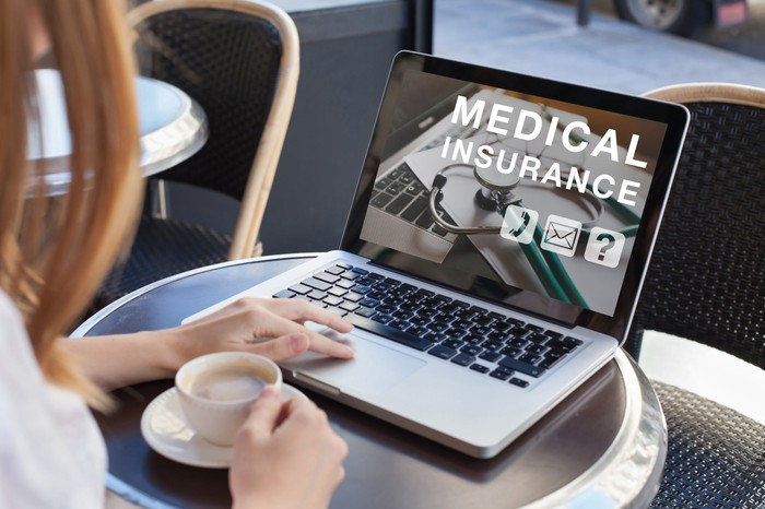 Woman with cup of coffee looking at medical insurance screen on her laptop.
