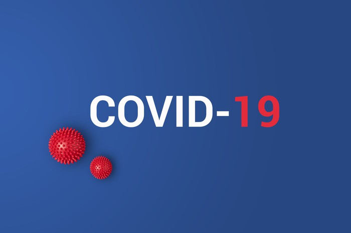 COVID-19 printed on a blue background with small red models of the novel coronavirus