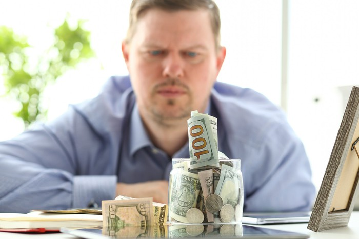 Man staring at a jar stuffed with cash.