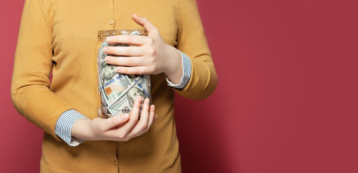 A person holding a jar of cash.