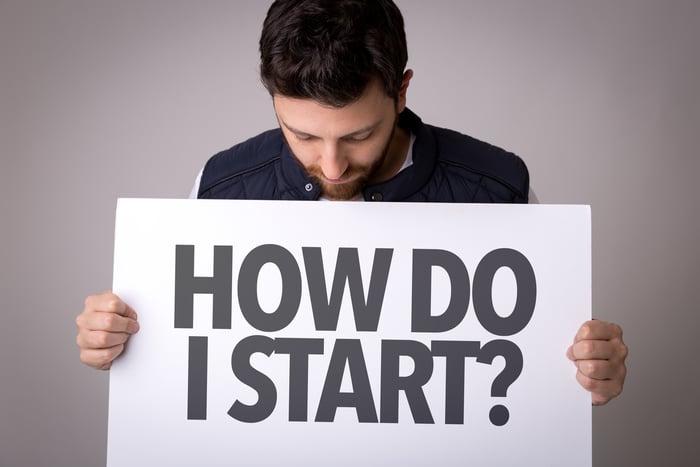 "Man holding sign that reads, ""how do I start?"""