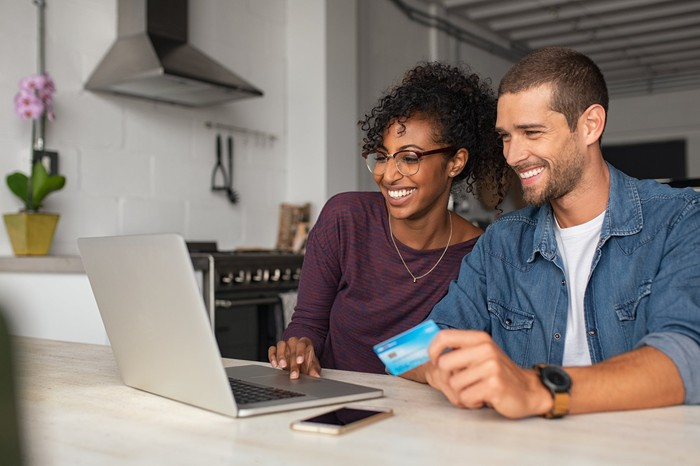 A young couple smile at the laptop as the man holds a credit card in their kitchen.
