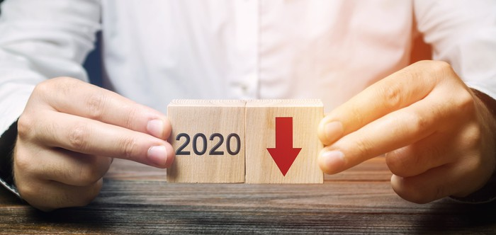 An investor holds blocks marked 2020 with an arrow pointing downward.