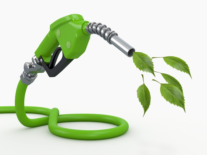 Green fuel pump with leaves exiting nozzle, indicating biofuel.