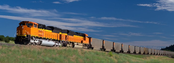 A yellow freight train ascends a hill under blue skies in Colorado.