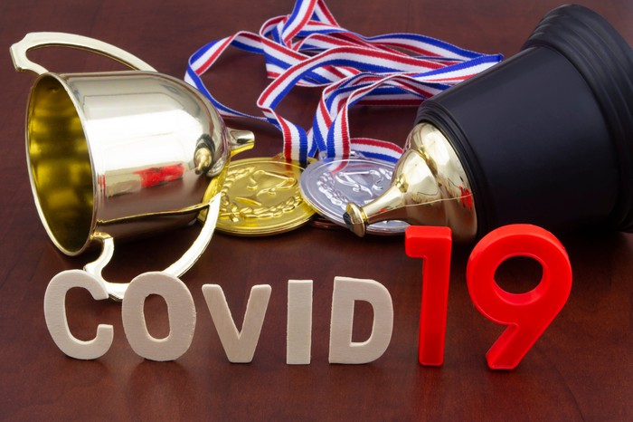 COVID-19 spelled out in front of a trophy, gold medal, and silver medal