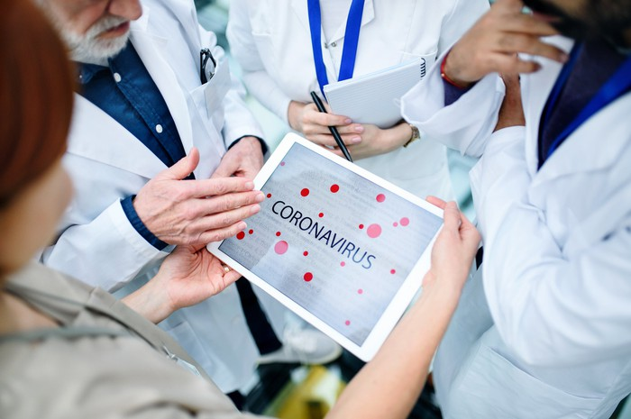 "Four people wearing white coats standing in a circle around a touchscreen tablet displaying ""coronavirus"""