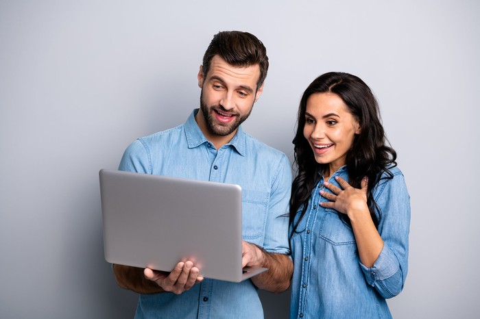 Man and woman smiling while looking at the screen of a man holding a laptop