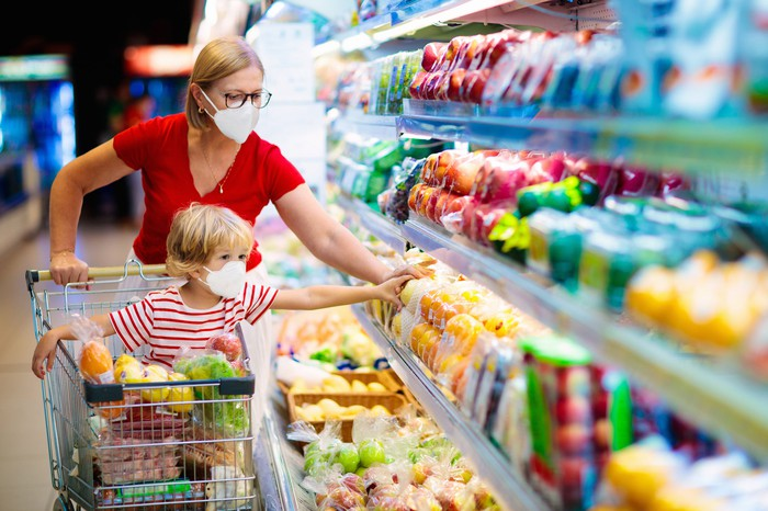 woman and child grocery shopping with masks