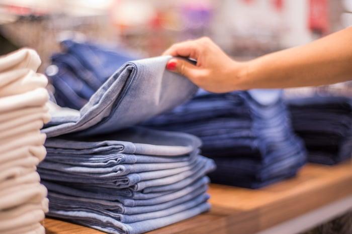 Stacks of denim jeans on store shelves