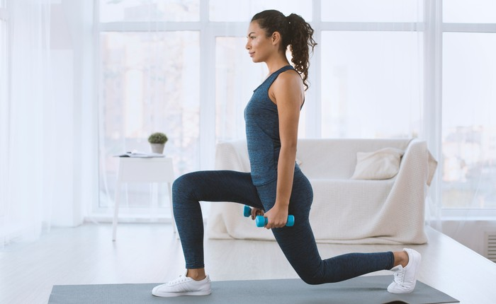 Woman doing lunges with hand weights at home.