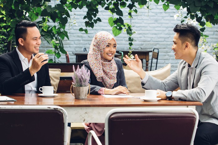 A woman and two men at a table talk and smile.