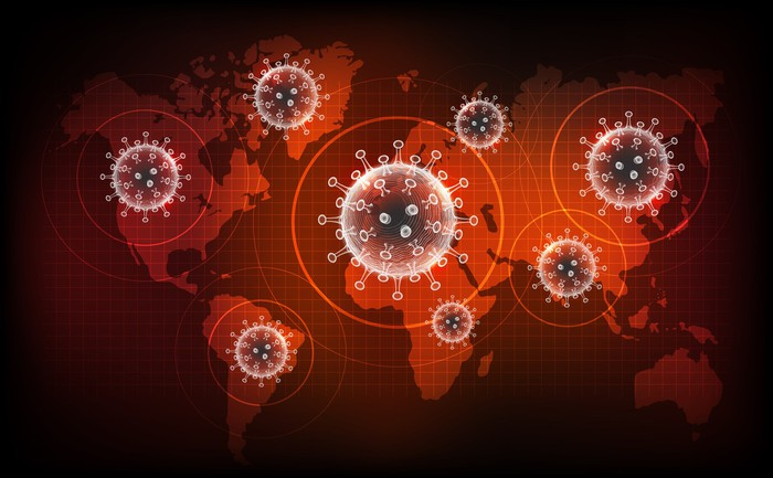 Enlarged coronavirus particle icons superimposed over map of the Earth, rendered in various shades of red