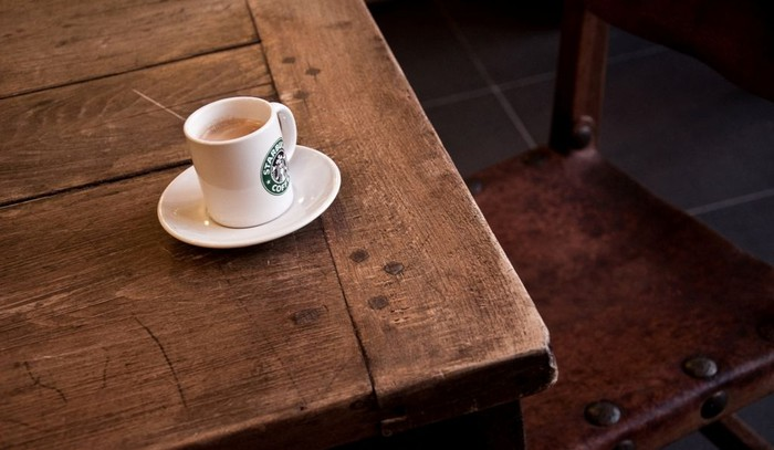 A Starbucks coffee cup sitting on a table.