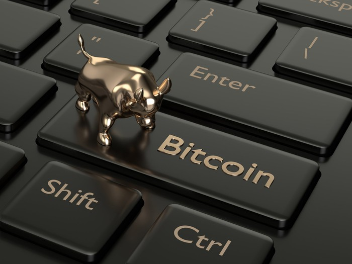 A miniature gold bull is on top of a keyboard button labeled bitcoin.