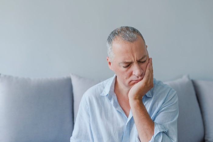 Older man holding his face and closing his eyes
