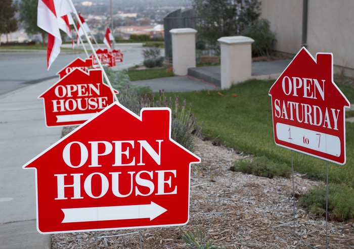 Open House signs displayed along a sidewalk.