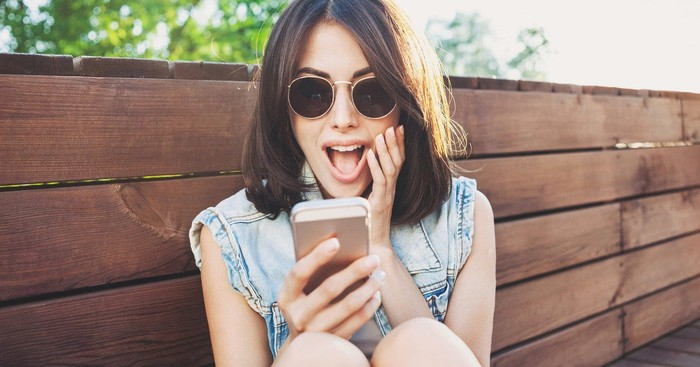Woman looking at her smartphone with a surprised expression on her face