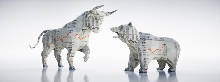Paper figurines of a bull and a bear facing each other.