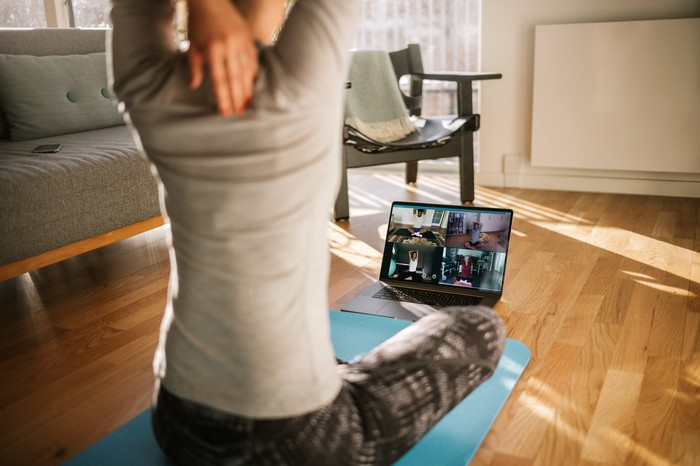 Woman doing yoga with a computer in an apartment.