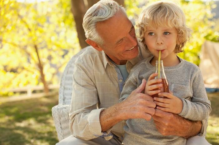 A little boy drinks a soda in his grandpa's lap outdoors.