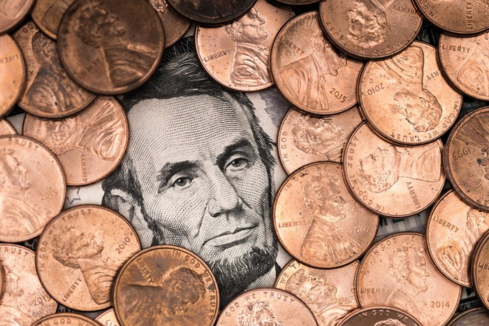A pile of pennies surrounding Abraham Lincoln's face on a five-dollar bill.