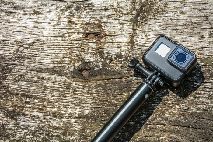 An action camera lying on a wooden plank.