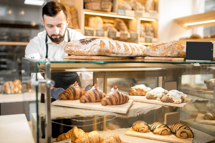 Man in apron arranging bakery case