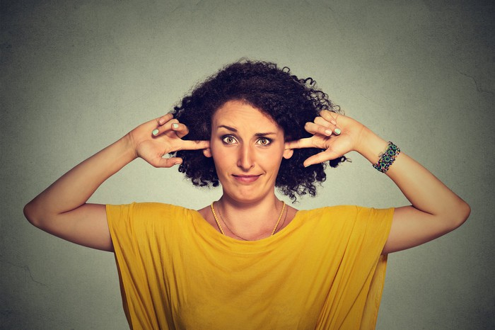Woman not listening by holdings fingers in her ears