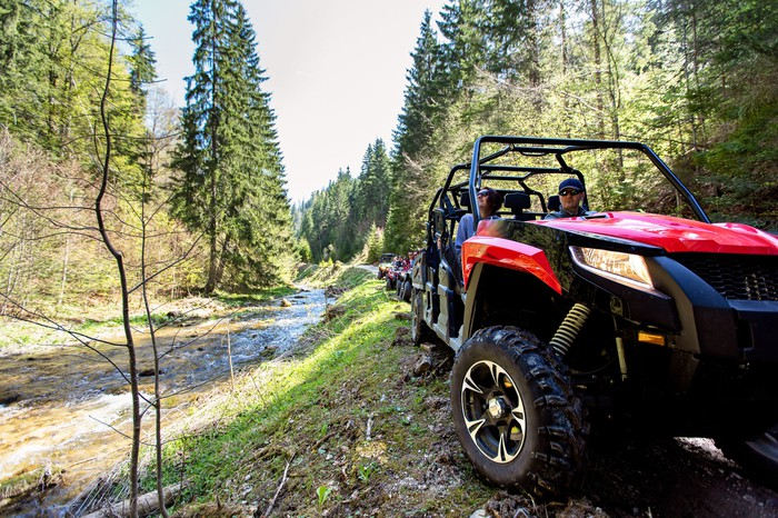 Group of ATVs riding on a wooded trail.