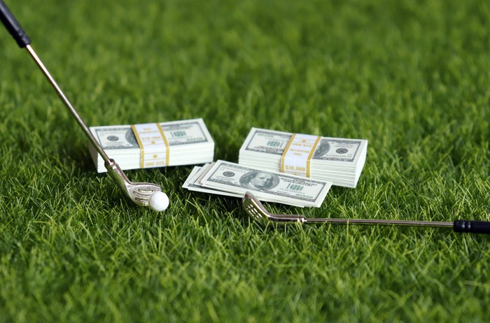 golf clubs and money on green grass implying betting on golf
