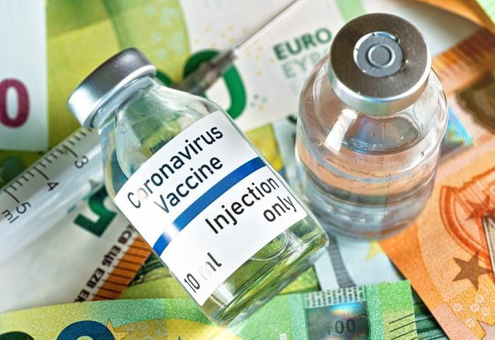 A pair of coronavirus vaccine vials sit on top of currency bills.