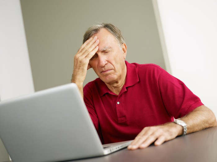 Older man at laptop holding his head.