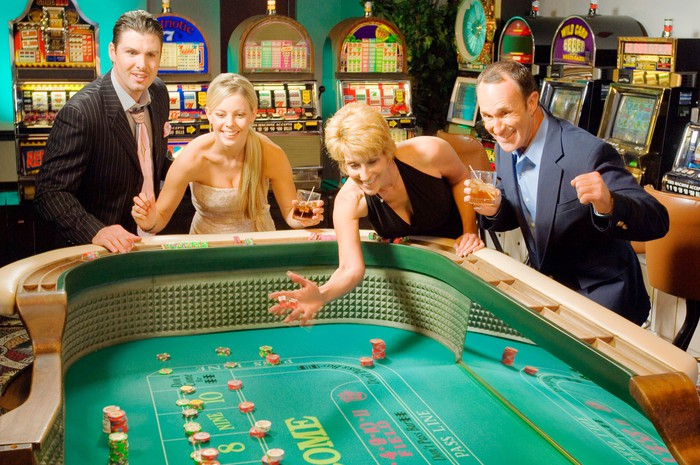 Happy gamblers rolling dice at a craps table.