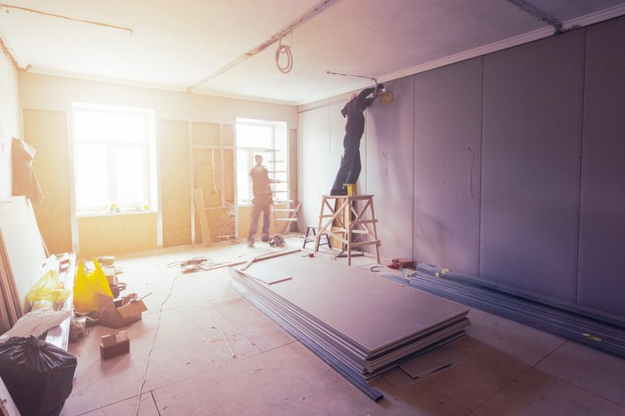 Drywall installation at a construction site.
