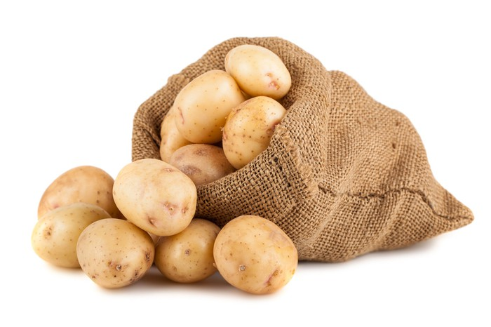 A sack of potatoes with potatoes sitting next to it