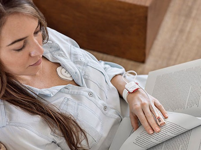 Masimo SafetyNet with Radius PPG and Radius T on a woman reading a book.