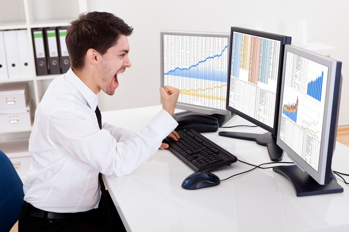 A cheering equities trader pumping his fist while looking at charts on his computer screens.