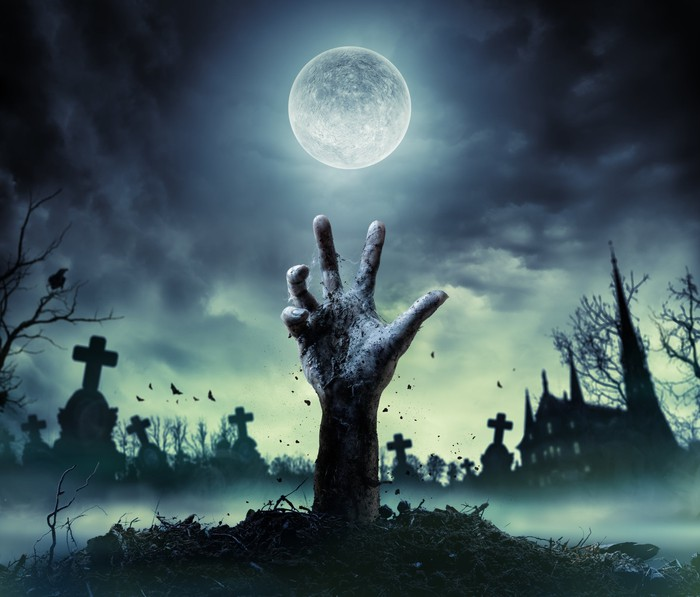 A zombie hand rising from a grave against a full moon.