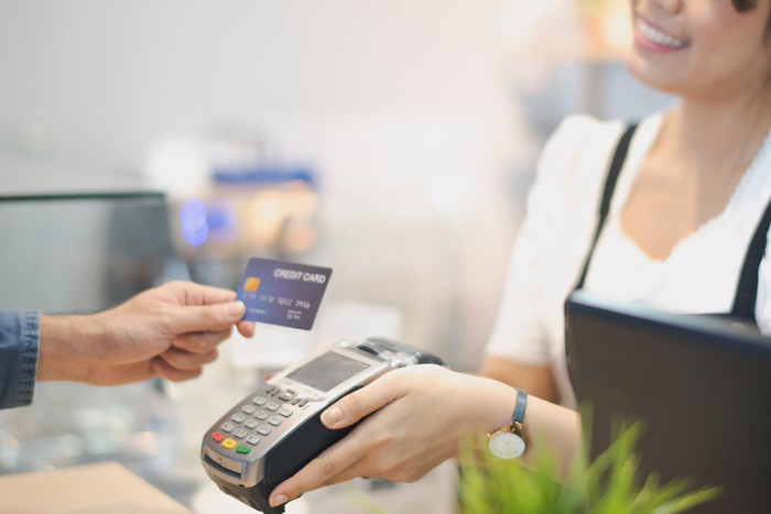 A person paying a vendor with a credit card as she holds up a card-swipe device.
