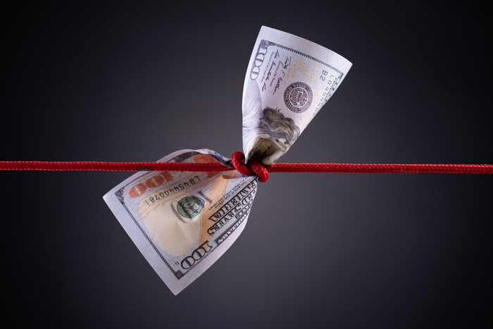 A red string knotted around a hundred-dollar bill.